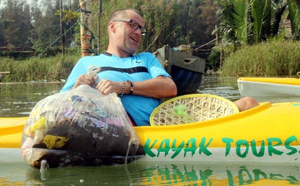 """Ông Paul Lasenby vất vả đưa bao rác khá lớn lên thuyền. """"Tôi mong muốn ở Việt Nam có nhiều hoạt động du lịch như thế này để người dân ý thức về chuyện xả rác ra môi trường đã gây ô nhiễm cho các dòng sông"""", ông Paul nói."""